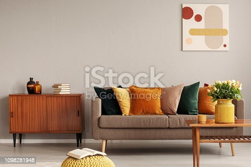 Books and vases on retro cabinet next to comfortable sofa with pillows