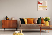 istock Books and vases on retro cabinet next to comfortable sofa with pillows 1098281948