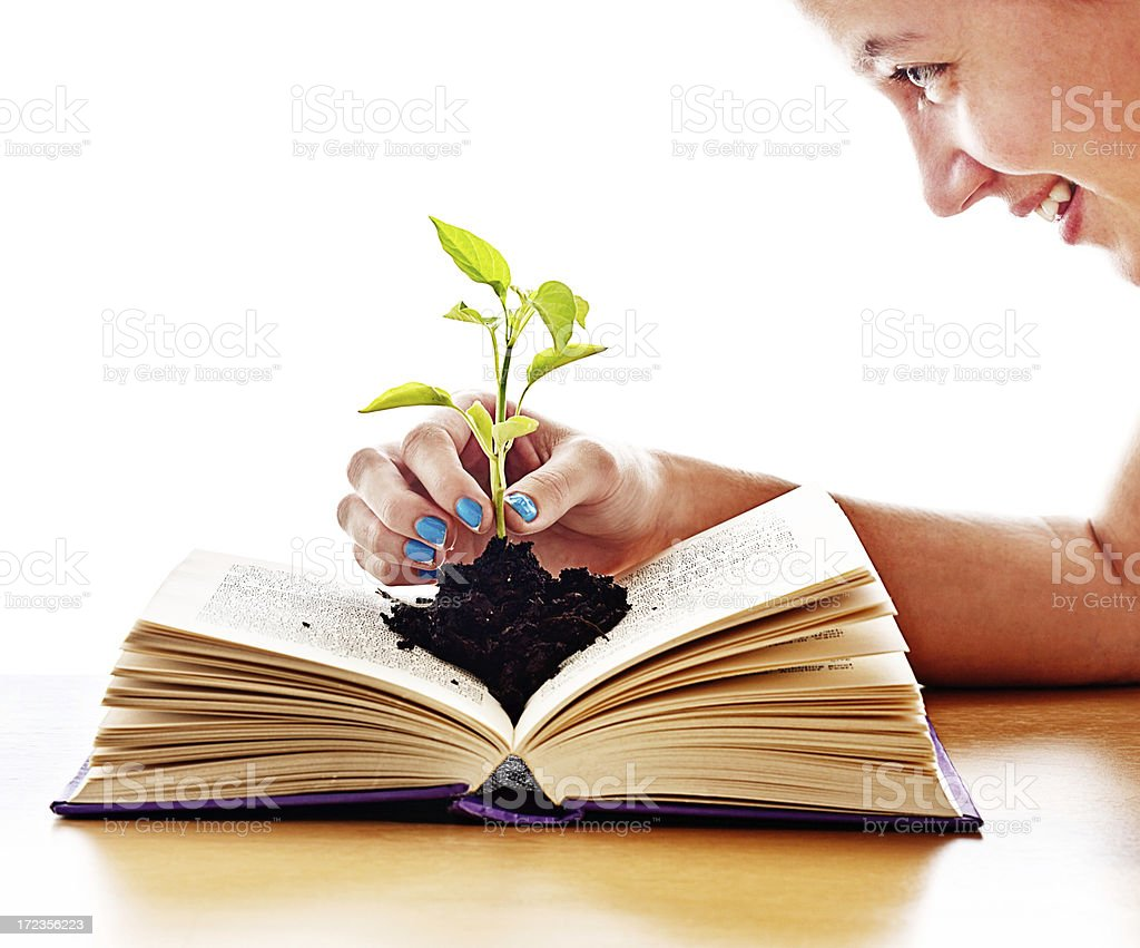 Books are inspirational! Woman smiles at seedling growing from book royalty-free stock photo