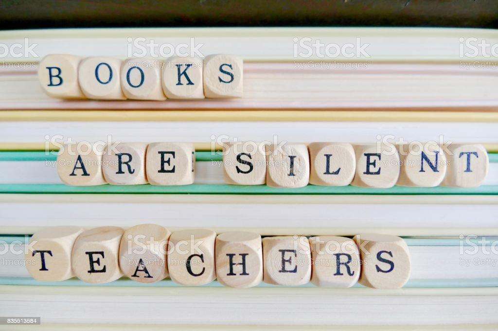 Los libros son maestros silenciosos: cartas sobre una pila de libros - foto de stock