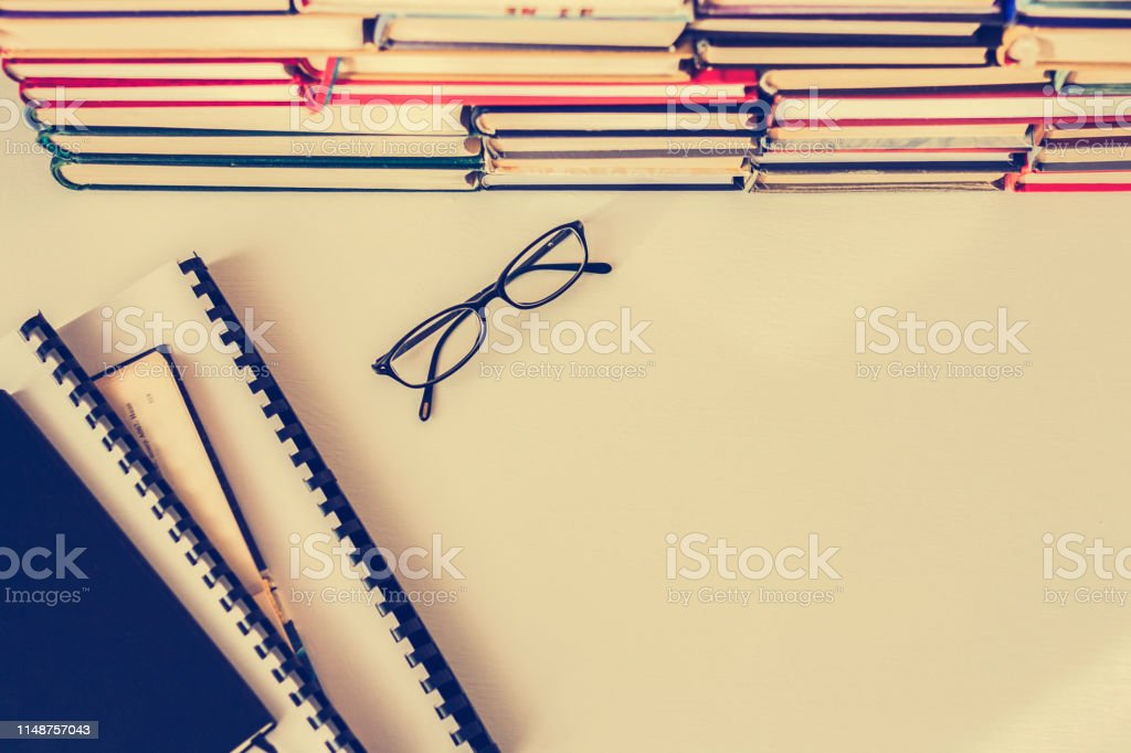 Books background, glasses and textbooks on white wooden table.