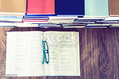 istock Books background, open book and glasses on wooden table in office for education learning concept 1174777634