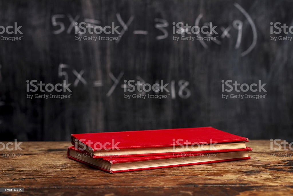 Books by blackboard with equation royalty-free stock photo