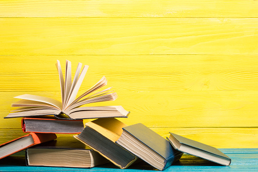 Books composition with vintage old hardback diary, fanned pages on wooden deck table and yellow background. Books stacking. Back to school. Copy Space. Education background