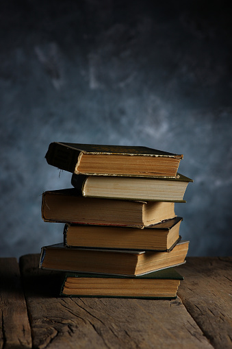 Pile of various books on wooden background