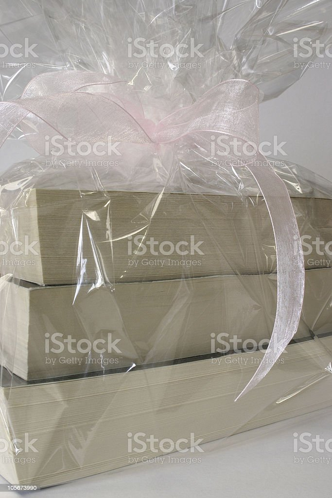 Three paperback books gift wrapped in clear cellophane with pink...