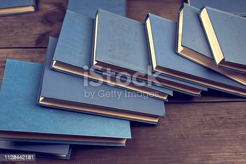 istock books in a blue cover on a brown wooden table 1128442181