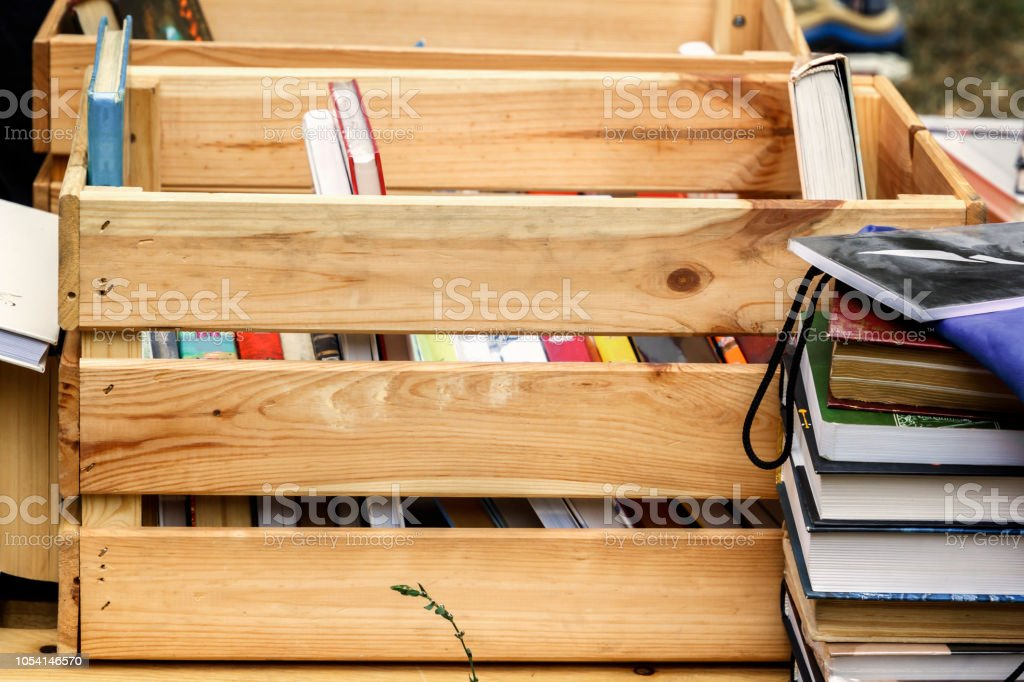 Books in a wooden box are prepared for sale at a street fair stock photo