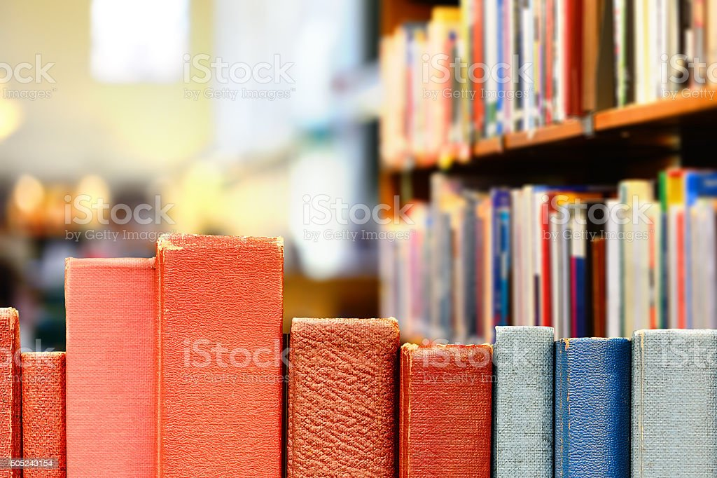 Books in row, library shelves in background stock photo