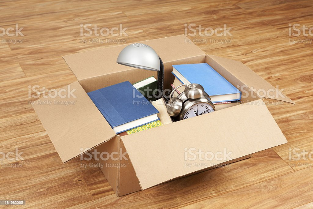 \'Books, lamp, and alarm clock in a cardboard box. Moving house or...