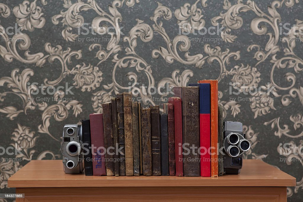 Books leaning on cameras for cinema and literature concept royalty-free stock photo