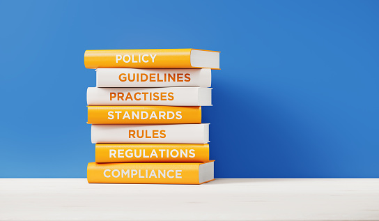 Books of compliance, regulations, rules and guidelines are sitting on top of each other. The books have unique texts on their spines related to compliance subject.