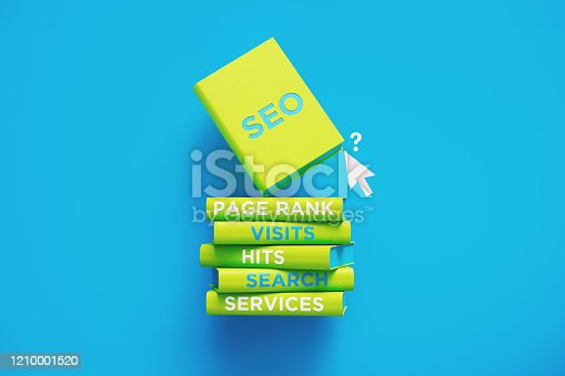Books of SEO page rank visits hits and search are sitting on top of each other over blue background. The books have unique texts on their spines related to SEO subject and are sitting next to a computer cursor.