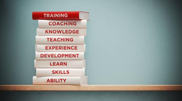 livros de treinamento e desenvolvimento na parede cinzenta dianteira - habilidade - fotografias e filmes do acervo