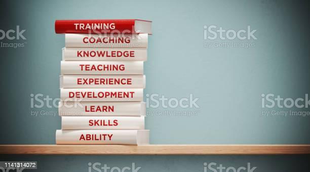 Books Of Training And Development In Front Grey Wall — стоковые фотографии и другие картинки Без людей