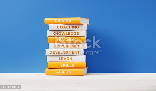 Books of training, development  and skills are sitting on top of each other. The books have unique texts on their spines related to training  subject.