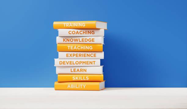 Bücher über Ausbildung und Entwicklung vor der blauen Wand – Foto