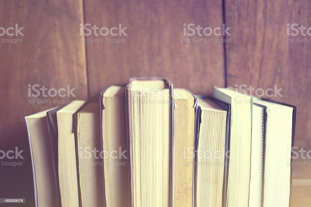 Books on a wooden background, vintage color effect stock photo