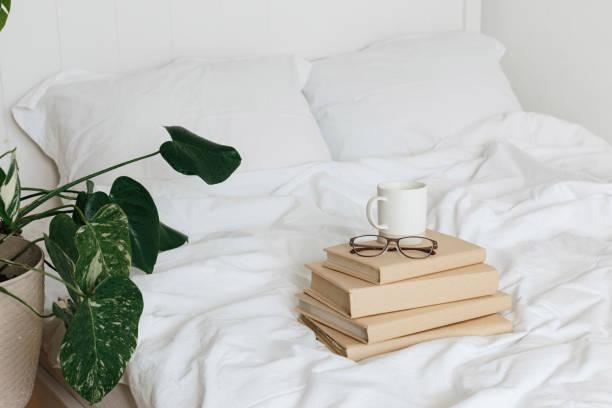 Bücher auf Bettwäsche weiße Bettwäsche. – Foto