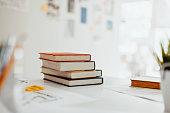 Books on desk in bright modern business design office