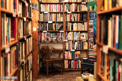 An array of book titles under a variety of category headings on bookshelves above a wooden chair in the corner of a San Francisco second-hand bookstore.