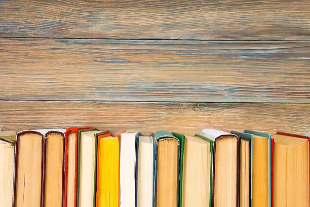 Books on grunge wooden table desk shelf in library. Back - foto de stock