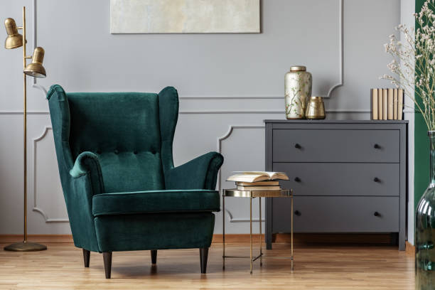 Books on stylish golden small table next to emerald green velvet wing back chair in grey living room interior Books on stylish golden small table next to emerald green velvet wing back chair in grey living room interior armchair stock pictures, royalty-free photos & images
