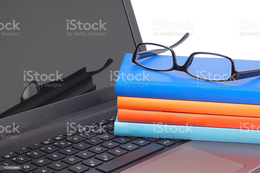 books on the laptop keyboard with glasses royalty-free stock photo