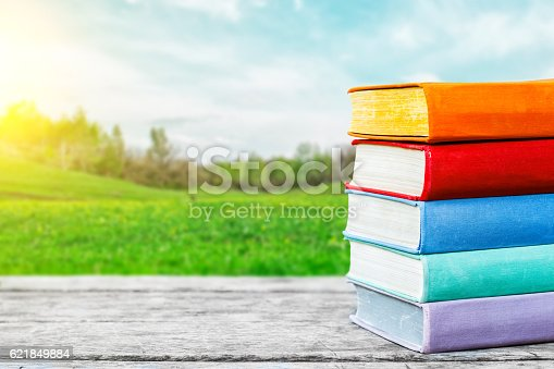 815359666 istock photo Books on the old wooden table at the nature background 621849884