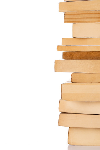 Stack of books on wooden chair in living room.