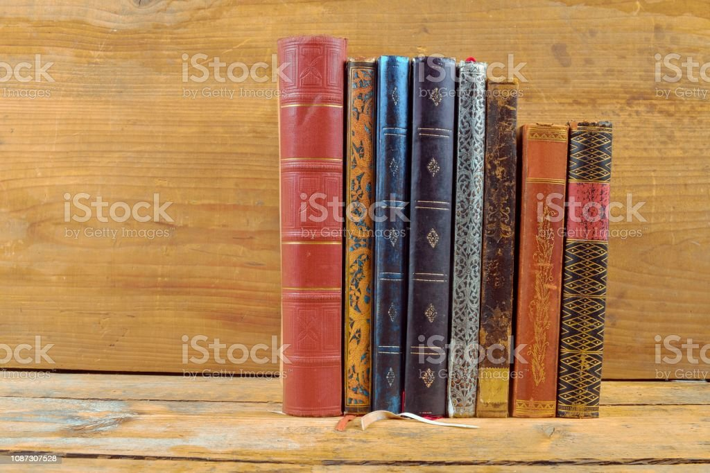 Books on wooden background. Old vintage books on wooden brown background. Copy space. Concept of the reading, education and still life stock photo