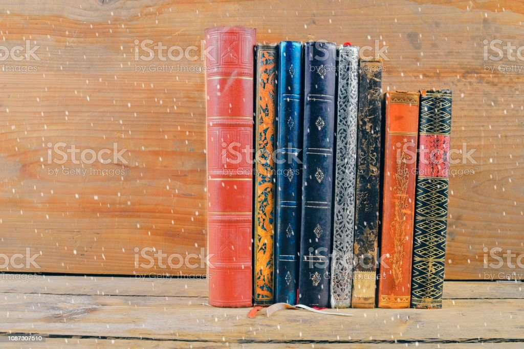Books on wooden background over snow effect. Old vintage books on wooden background. Copy space. Concept of the reading, education and still life stock photo