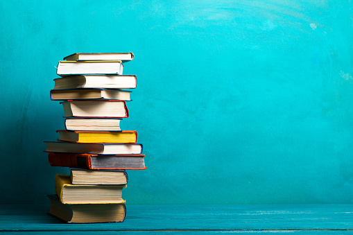 Back to school and education concept. The stack of books on the wooden background and place for text.