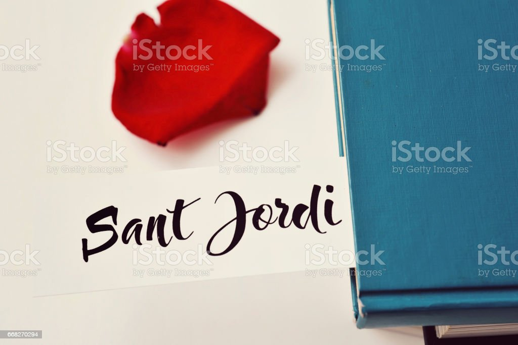 books, red rose and text Sant Jordi stock photo