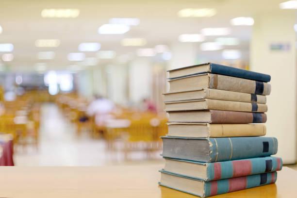 Pilha de livros na mesa de madeira na biblioteca com espaço de cópia. - foto de acervo