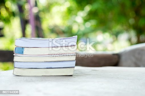 istock Books stacked on blurred garden 862744306