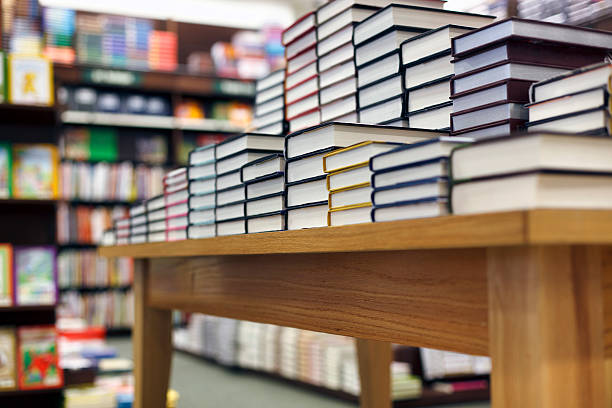 Books stacked on table at bookstore Stack of books on display at the bookstore hardcover book stock pictures, royalty-free photos & images