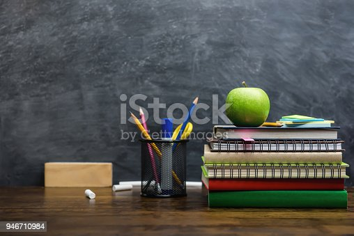 istock Books, stationery and education supplies on wooden desk in classroom 946710984