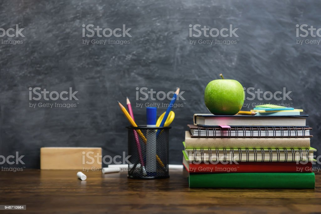 Books, stationery and education supplies on wooden desk in classroom stock photo