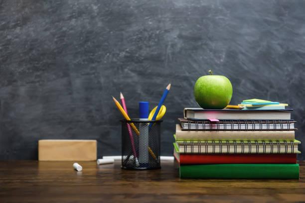 bücher, schreibwaren und bildung liefert auf hölzernen schreibtisch im klassenzimmer - kreide farbe schreibtisch stock-fotos und bilder