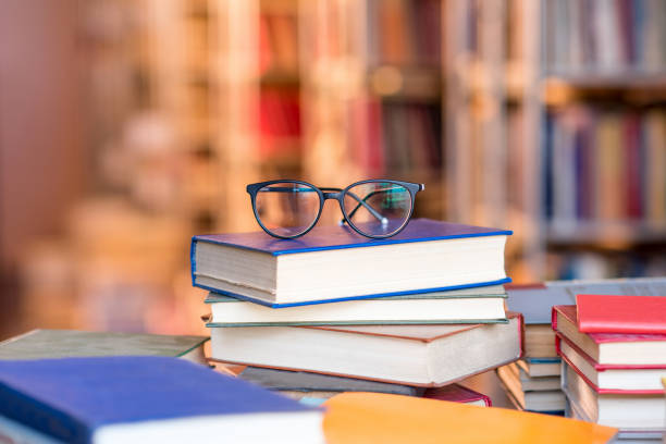 Books with eyeglasses at the library stock photo