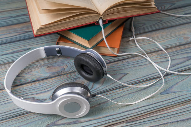 Books with headphones on a wooden table. stock photo