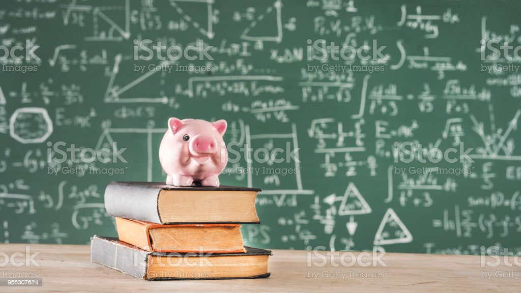 Books with piggy bank in front of green chalk board stock photo