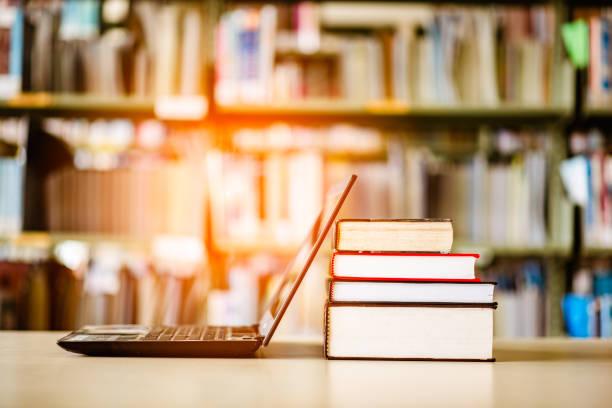 bücherregale und laptops befinden sich auf dem schreibtisch bibliothek. - geführtes lesen stock-fotos und bilder