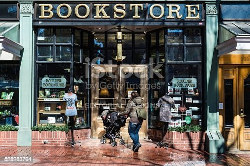 Boulder, Colorado, USA - March 10, 2013: A person with baby carriage approaches a bookstore at the Historic Pearl Street Mall, a pedestrian zone full of shops and restaurants and a popular tourist attraction.