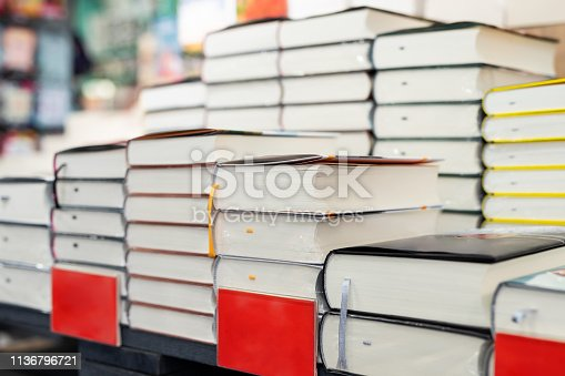istock Bookstore shelf with pile of new books with red empty plate. New arrivals at bookshop. Presentation of book. Copyspace 1136796721