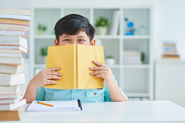 Bookworm Cheerful schoolboy hiding his smile behind book child prodigy stock pictures, royalty-free photos & images