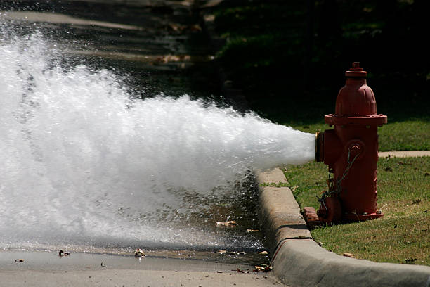 Booom! A photograph taken of a fire hydrant releasing some pressure one hot Oklahoma day. fire hydrant stock pictures, royalty-free photos & images