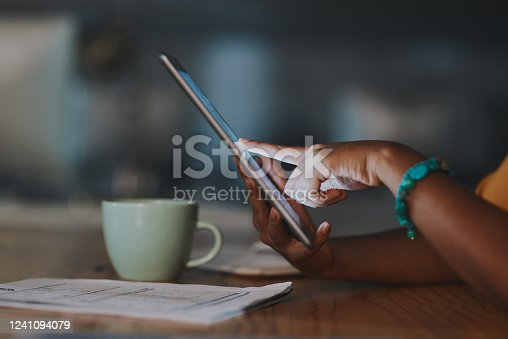Closeup shot of an unrecognisable businesswoman using a digital tablet in an office at night