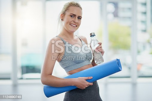 Portrait of a sporty young woman holding a yoga mat and a water bottle in a studio
